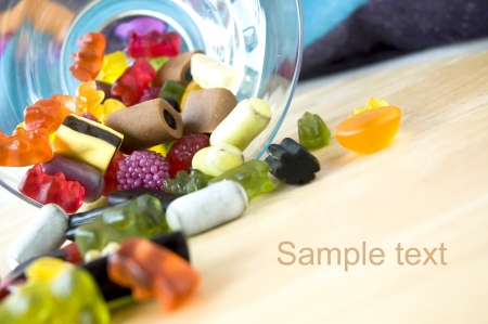 variety candies pouring from glass background with space for text photo