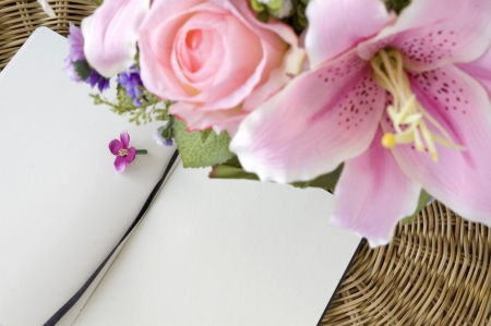 pink flowers put with notebook blank page