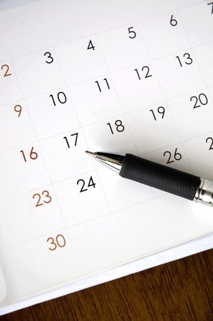 booking: pen point to date on calendar Stock Photo