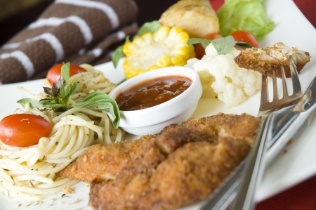 fried chicken on fork put on dish with pasta and salad photo