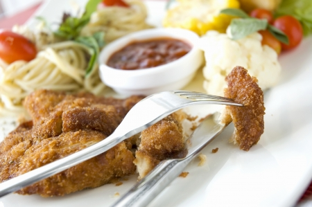 piece of fried chicken on fork with salad and pasta background Stock Photo