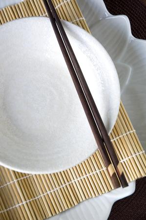 white dish with chopstick on bamboo mat photo