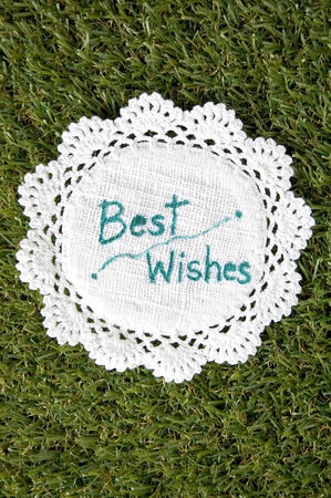best wishes: best wishes on white fabric put on green grass Stock Photo