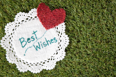 best wishes: wording best wishes on fabric with red heart put on grass