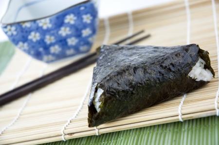 origini japanese rice ball on bamboo mat