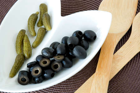gherkin pickles with black olives on plate photo