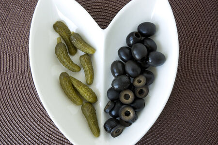 black olives and pickles serve on heart shape plate photo