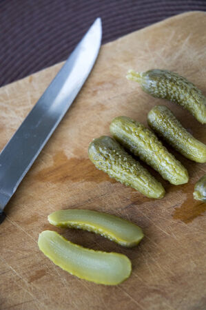 pickles sliced by knife on wooden board