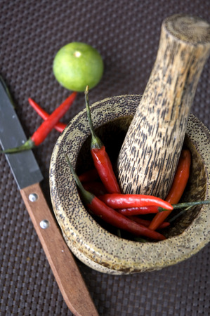 red hot chilli in wooden mortar with green lime and knife Stock Photo