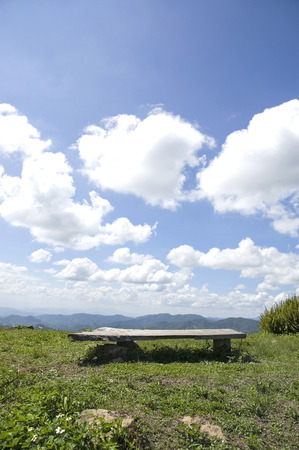 wooden bench on mountain with clear beautiful sky background photo