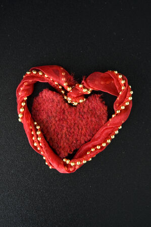 red fabric cut in heart shape on black background photo
