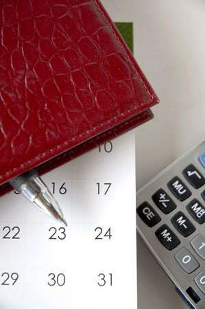 monthly salary: pen in red notebook put on calendar