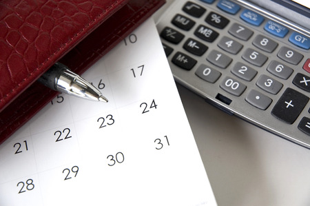 pen point to end of month on calendar beside calculator