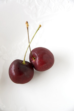 close up two sweet cherries on white plate