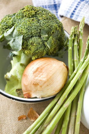 fresh broccoli onion and asparagus in kitchen photo