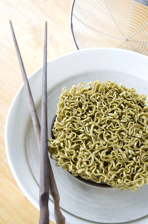 green vegetable raw noodles on bowl Stock Photo