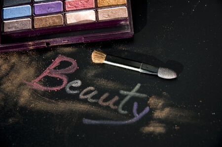colorful eyeshadow and brush with words beauty on black background photo