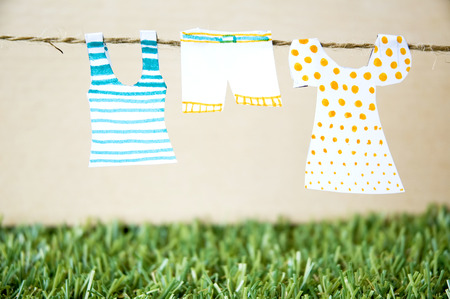paper clothes hanging on rope with green grass background photo