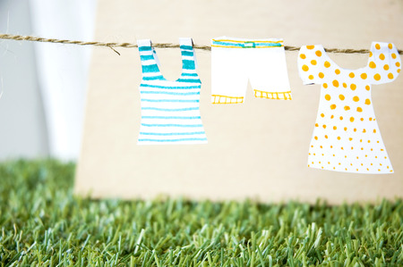 hanging paper clothes on rope with green grass background photo