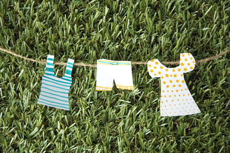 paper clothes hanging on rope put on green grass photo