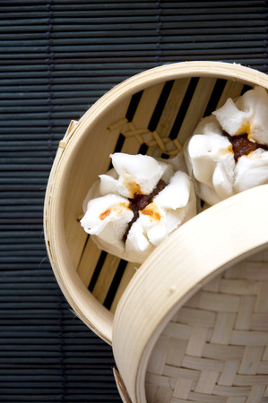 dim sum: salapao dimsum in bamboo mat on black background