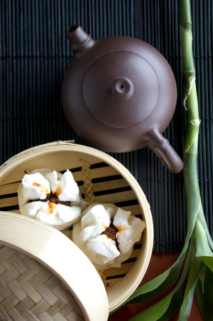 tea pot put beside salapao dimsum in tray photo