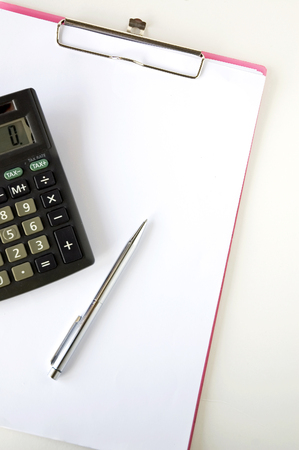 calculator with pen on white paper photo