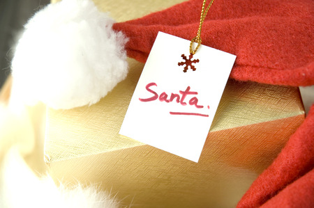 Close Up Santa Gift Tag On Golden Box With Santa Red Hat Stock Photo