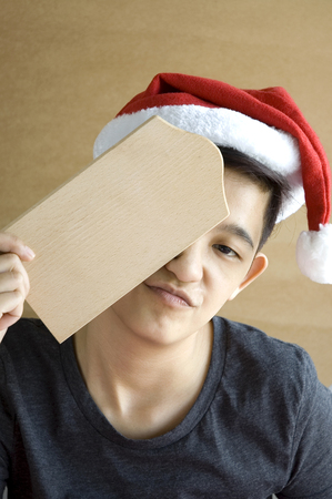 tomboy: asian chinese tomboy looks wear santa hat and holding blank wooden board for text with boring face Stock Photo