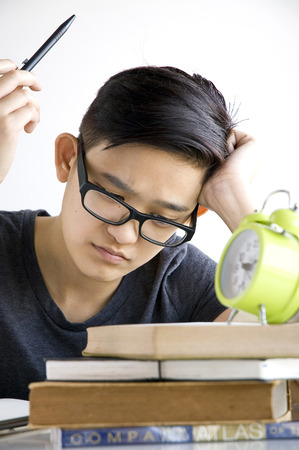 too many: tired asian student reading too many books