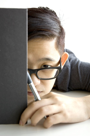 young asian wear specs holding pen and put a book cover her face half photo