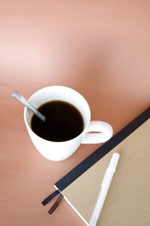 cup of black coffee with notebook beside photo