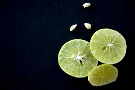 pieces of green lime with seed on black background photo