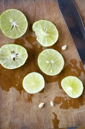 squeeze shape: slice fresh lime on wooden board with knife on background Stock Photo