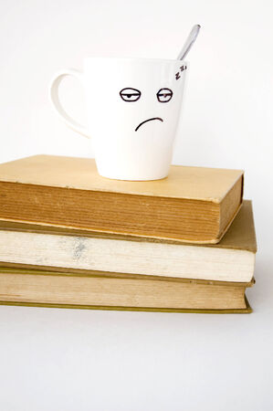 sleepy face coffee cup on stack of old books Stock Photo