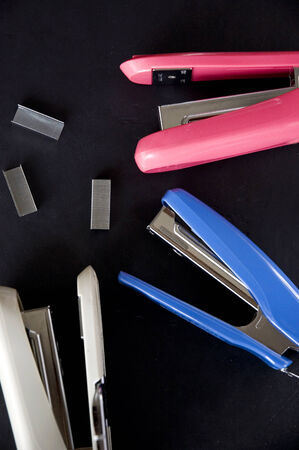 staplers: three color staplers on black background