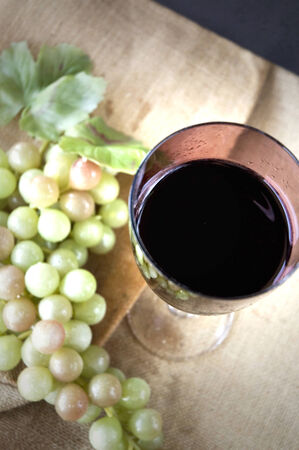 top view of red grape juice glass with grape background