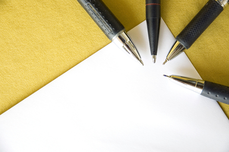four black pen point to angle of paper on yellow background photo