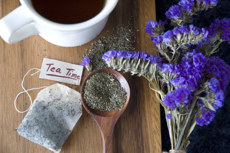 tea bag: peppermint tea on spoon and tea bag with tea time tag on wooden background