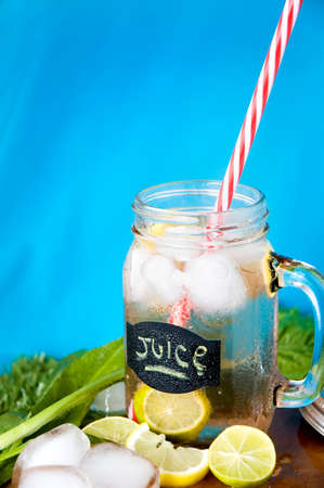 red straw: lemon juice with red straw on blue background