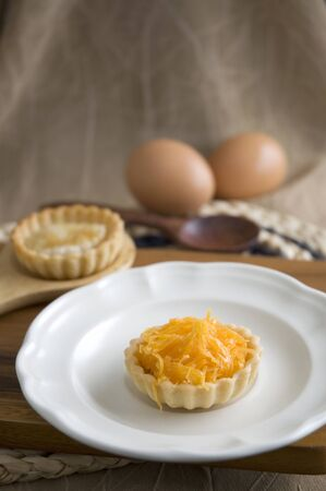 recipe decorated: sweet mini pie on dish with eggs on background