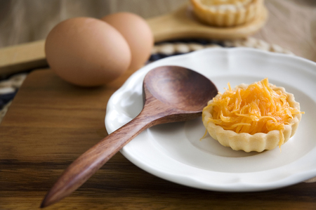 recipe decorated: golden sweet mini tart serve on white plate with wooden spoon