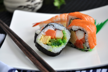 sushi chopsticks: close up sushi roll with chopstick serve on white plate Stock Photo