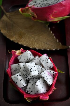 a portion: portion of fresh dragon fruit put on wooden tray Stock Photo