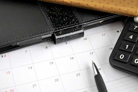 date book: pen point to date on calendar with calculator and organizer book on desk