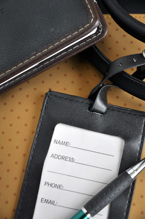 luggage tag: blank leather luggage tag with pen put on organizer book Stock Photo