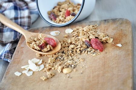 spilling: granola with dried berry on spoon spilling on wooden board Stock Photo