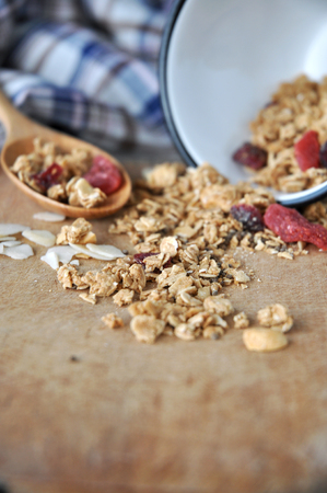 spilling: granola bowl spilling on wooden cutting board Stock Photo