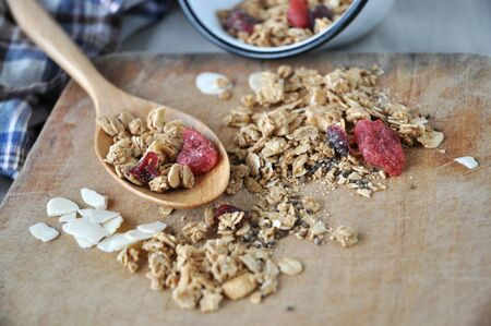 spilling: granola with dried berry spilling on wooden board Stock Photo