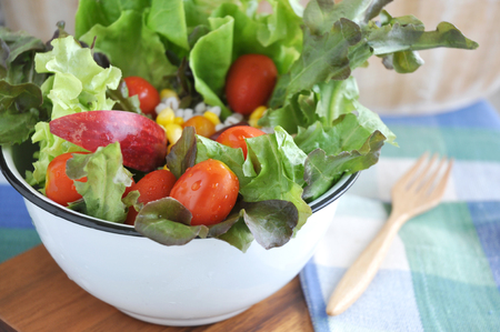 mixed vegetables: Close up fresh salad in big bowl put on wooden board Stock Photo
